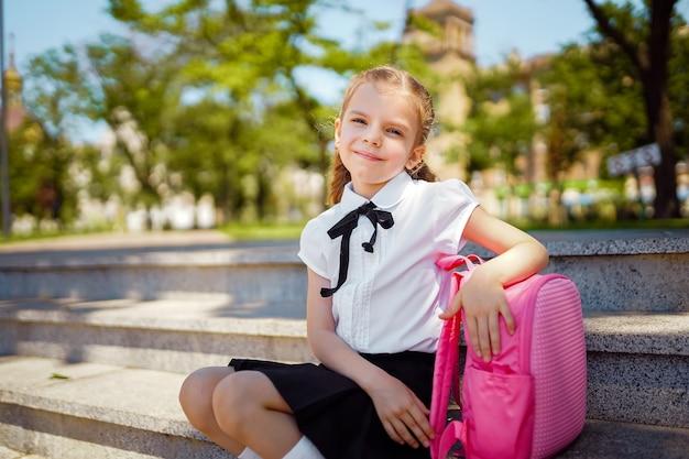 Ученица начальной школы, сидя на лестнице, кладет руку на портфель
