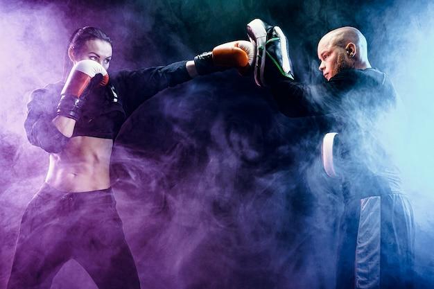 Женщина, осуществляя с тренером на уроке бокса и самообороны