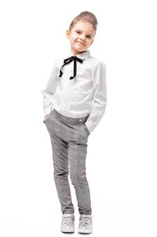 Красивая маленькая девочка в белой рубашке и серых брюках