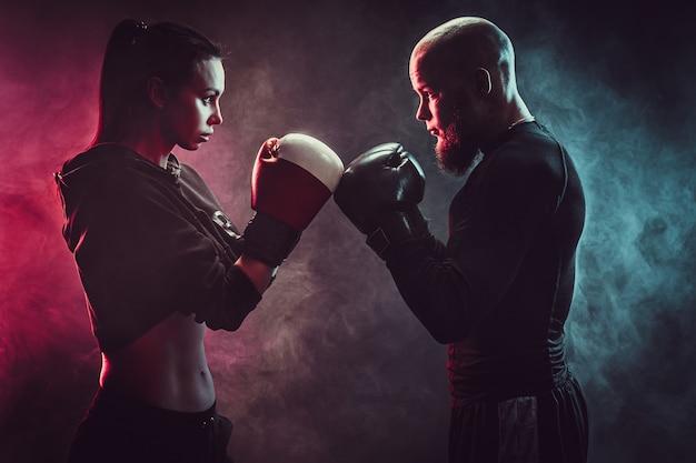 ボクシングと自己防衛のレッスンでトレーナーと運動している女性は積極的にお互いを見てください。前に立って。
