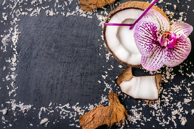 Кокосы с кокосовой стружкой и орхидеи на сером фоне камня