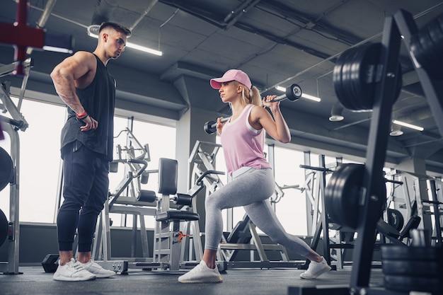 ハンサムなパーソナルトレーナーがジムで彼女を監視しながら脚のエクササイズを行うスポーツウェアで集中してやる気のあるスポーティな若いブロンドの女性