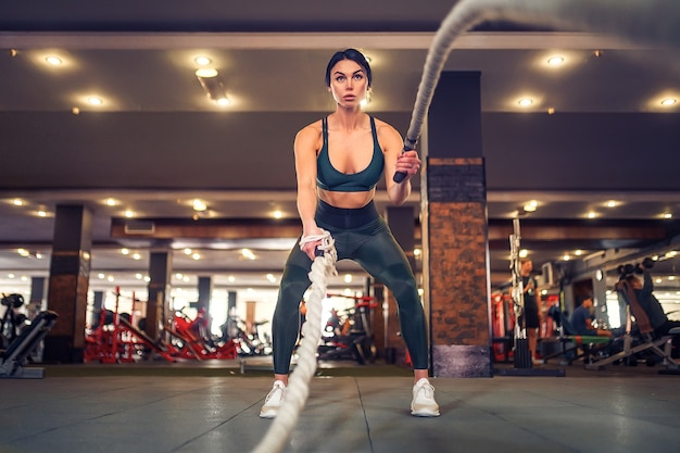 Подходит женщина, одетая в спортивный костюм, позирует с боевыми канатами в тренажерном зале