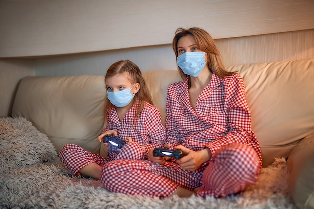 Женщина и молодая девушка в пижаме и медицинских защитных масках сидят на софте с игровыми контроллерами