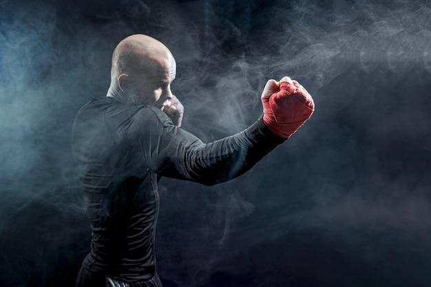 Боксер спортсмена воюя на черной стене с дымом. бокс концепция спорта