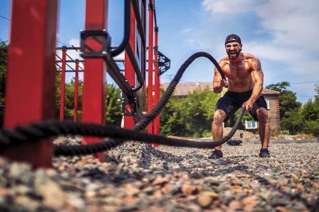 Человек усердно работает с веревкой, функциональные тренировки