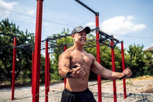 Фитнес человек обучение грудь с сопротивления полос на улице тренажерный зал двор. тренировка на открытом воздухе. тренировка тела с оборудованием на улице. эластичный резиновый аксессуар.