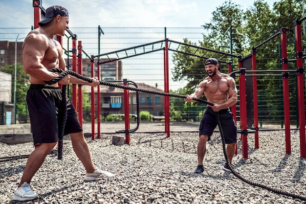 男性は、通りのジムの庭でロープで一生懸命働きます。屋外トレーニング。フィットネス、スポーツ、運動、トレーニング、ライフスタイルのコンセプト。