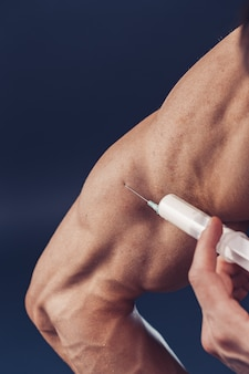 ボディービルダーはビタミンの注射になります。暗い背景に完璧な体格を持つスポーティな男の写真。強さと動機