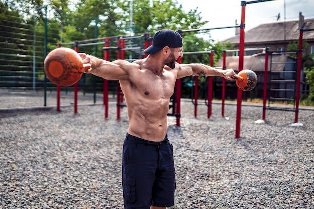 Спортивная (ый) человек работает с гирей на улице тренажерный зал двор.