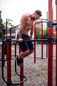 屋外のストリートジムで不均一なバーで腕立て伏せを行う強い筋肉の男