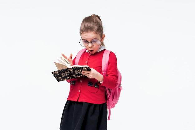 Восхитительная маленькая девочка в красной школьной куртке, черном платье, рюкзаке и закругленных очках удивила или удивилась, глядя на книгу, позируя на пустом месте. изолировать