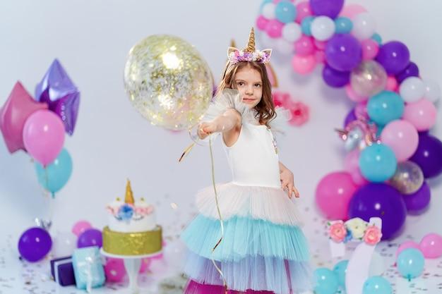 金の紙吹雪の気球を保持しているユニコーンガール。ユニコーン風の誕生日パーティーを飾るためのアイデア。フェスティバルパーティーガールのユニコーン装飾