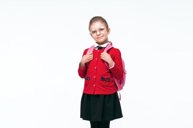 Очаровательны маленькая девочка в красной школьной куртке, черном платье, округлые очки, держась за ремни рюкзака и улыбается и смотрит в камеру, позирует на пустое пространство. изолировать