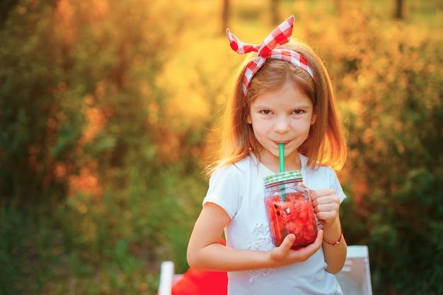 夏のさわやかなドリンクとして氷とミントの瓶にスイカレモネードを飲む子供。フルーツ入り冷たいソフトドリンク