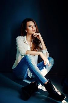 Красивая девушка сидит на полу в темноте