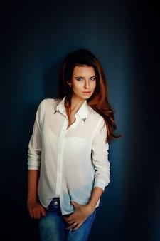 Красивая девушка стоит возле синей стены в темноте
