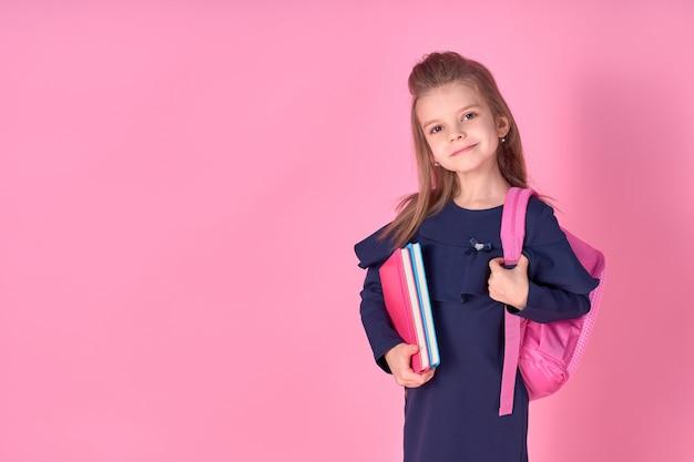 学校の制服のドレスとピンクの明るいバックパックを身に着けているノートブックで美しい巧妙な女の子
