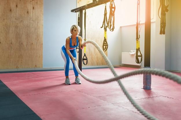 バトルロープを持つ女性は、フィットネスジムで運動します。スポーツウェアを着ている若い女性。