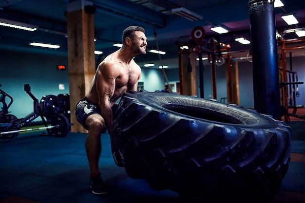 Человек без рубашки переворачивает тяжелую шину