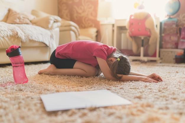かわいい女の子が自宅で体操を練習しています。