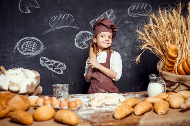Маленькая девочка замешивает тесто за столом
