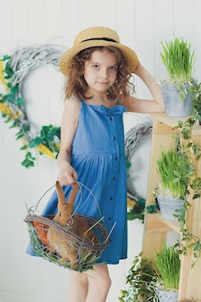 赤ちゃんウサギと遊ぶ幸せな笑い少女