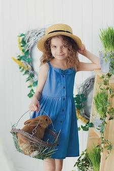 Счастливая смеющаяся маленькая девочка, играющая с маленьким кроликом