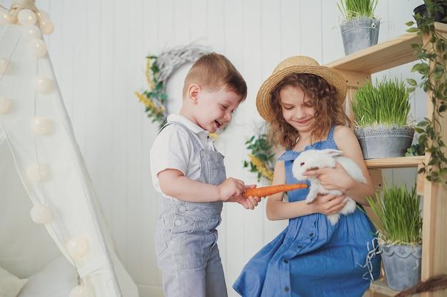 Счастливый смех маленькая девочка и мальчик, играя с маленьким кроликом