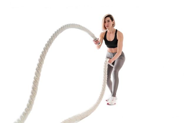 Женщина делает упражнения с боевой веревкой на белом