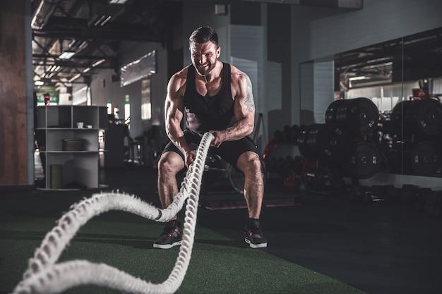 機能トレーニングジムでロープを持つ男性