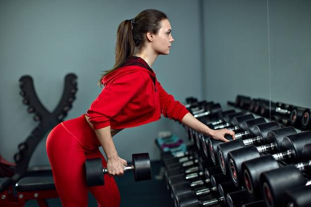 Красивая женщина, делать упражнения с гантелями в тренажерном зале.