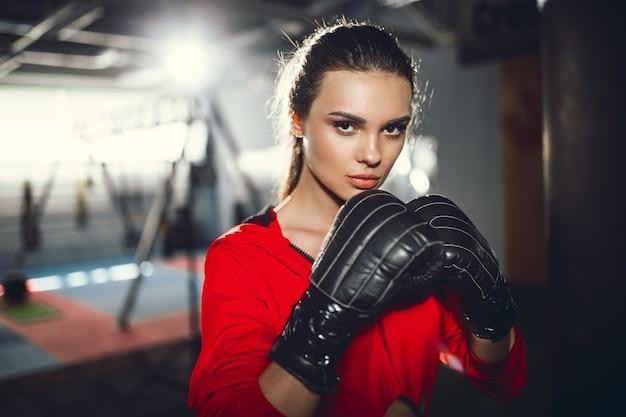 スポーツウェアでボクシングスリムな若い美しいブルネットの女性に合います。暗い薄明かり。