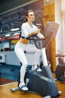 Крытый велоспорт женщина делает кардио тренировки на велосипеде в помещении тренажерный зал.