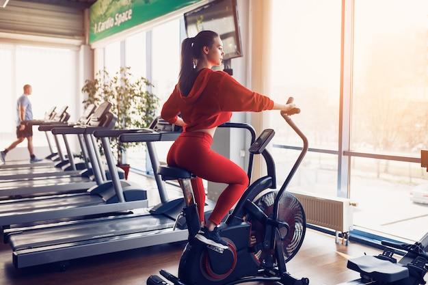 Женщина фитнеса используя воздушный велосипед для кардио тренировки в спортзале.