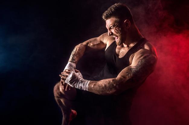 煙と黒い壁で戦うスポーツマンムエタイタイのボクサー。