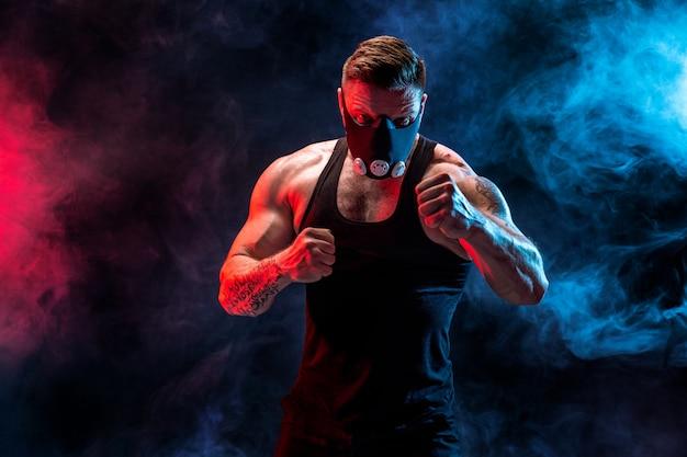 黒い壁に黒いトレーニングマスクで強い男性アスリート