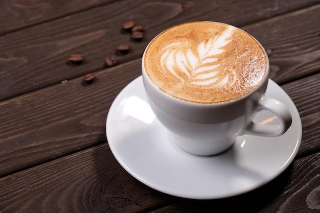 泡のクローズアップの写真とホットコーヒーのカップ