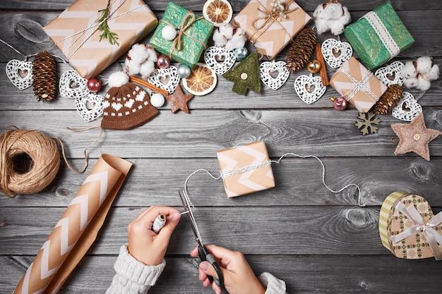 Творческое хобби. рождественские подарки с инструментами и украшениями. упаковка подарков на деревянный стол, вид сверху.