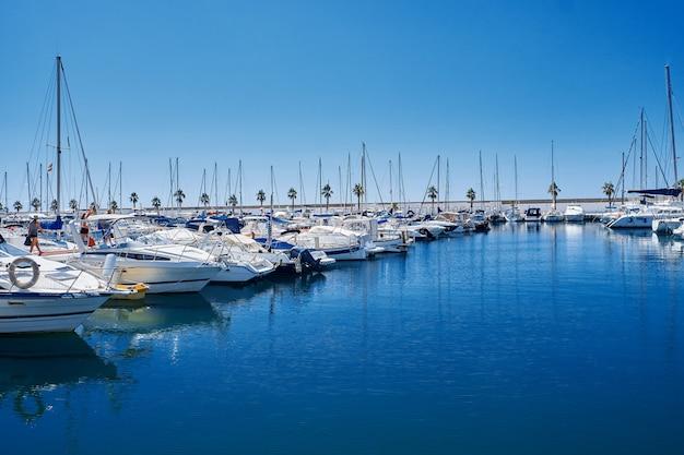 青い夕日の光、豪華な夏のクルーズ、余暇、アクティブライフ、休暇、休日の概念のヨット港ヨットと都市の港での反射。