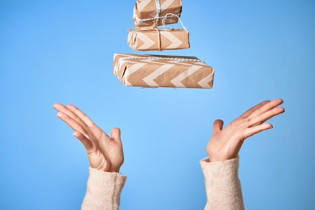 ギフトボックスをキャッチしようとする女性の手。クリスマスまたは新年の装飾ギフトボックス。