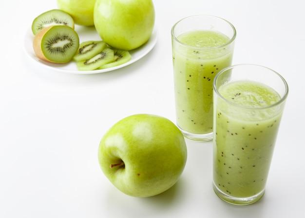 Здоровый зеленый пюре яблоко и киви на белом столе