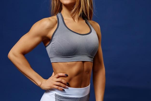 完璧なフィットネス体を持つ若いスポーツ女性の詳細