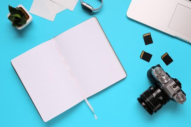 カメラ、ラップトップ、ノートブック、青い机の背景にあるメモリカードで構成される写真家のデスクトップの平面図-コピースペース。