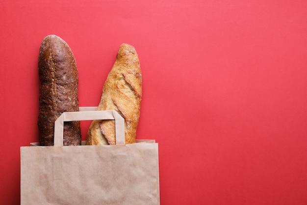 Свежий хлеб и багет в бумажной сумке на красном фоне. выпечка