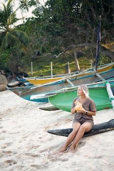 ブロンドの女性は木製のボートにココナッツ水を飲む