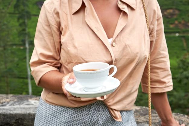 Женщина с чашкой напитка на плантации