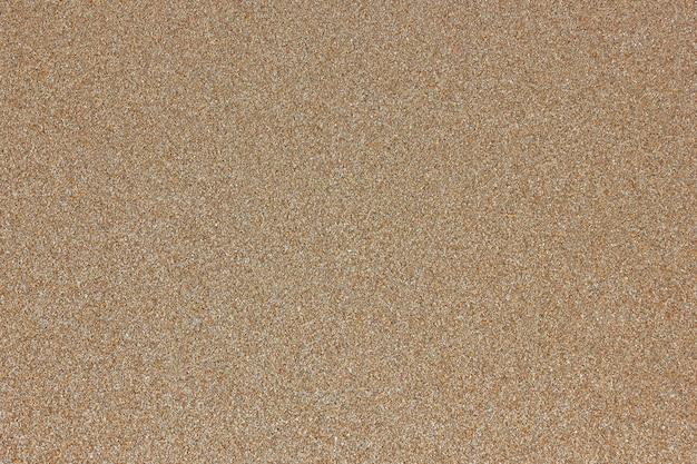 均質なベージュの黄色い砂の海洋構造の背景