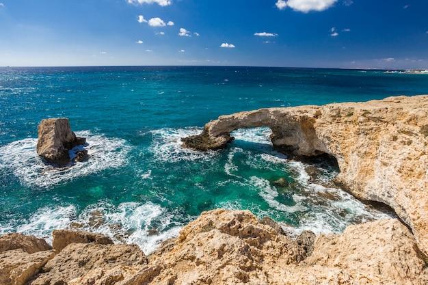 愛好家の橋またはモンクシールアーチ、アギアナパキプロスの地中海の石の崖。