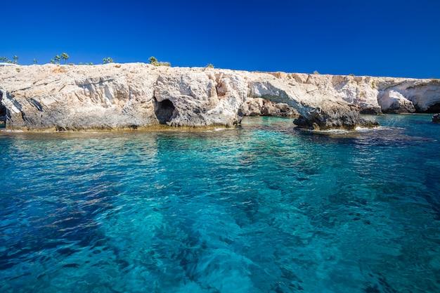 岩の多い海岸、澄んだ青緑色の水、青い空。